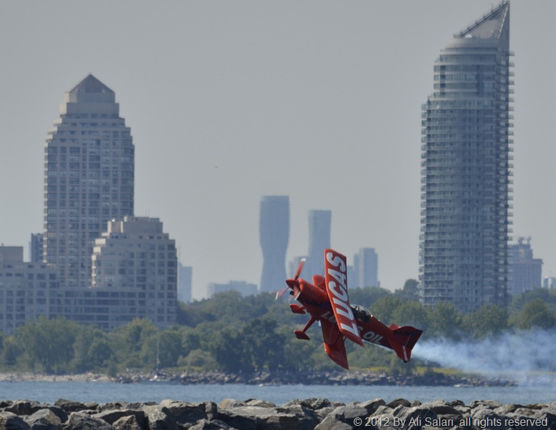 Picture of a Biplane flying low, with Mississauga's Marilyn Towers in the background